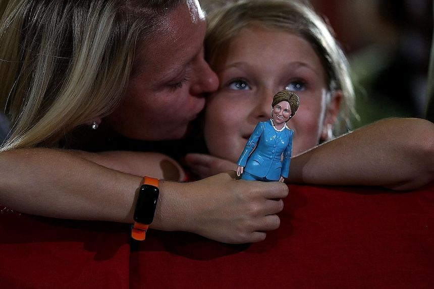 A young Clinton supporter (above) with a doll of the Democratic presidential nominee at a campaign rally in Ohio earlier this month, while a Trump supporter (below) waits for the Republican presidential candidate to speak at a campaign rally in the s