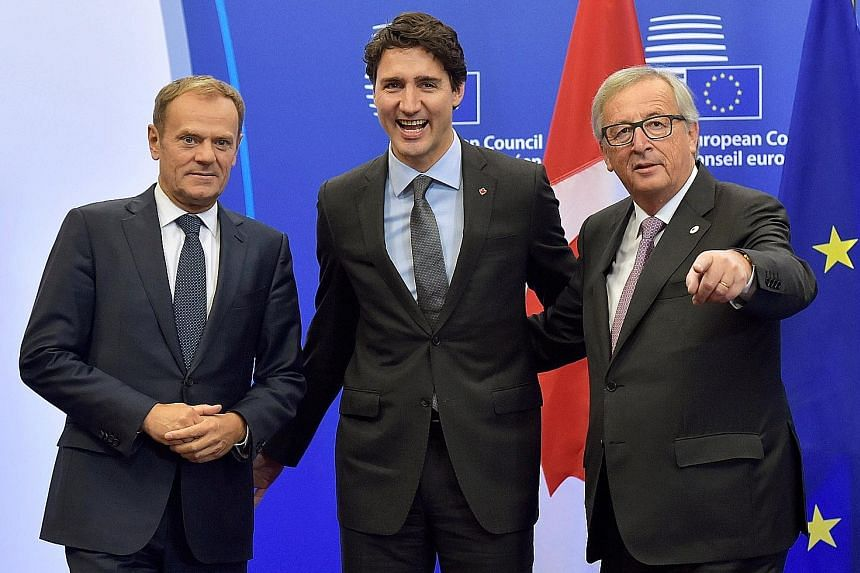Canada's Prime Minister Justin Trudeau (centre) with European Council president Donald Tusk (left) and European Commission president Jean-Claude Juncker in Brussels, before the signing of the deal yesterday.