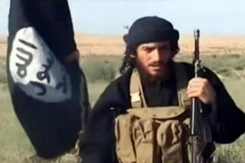 Spokesman for the Islamic State of Iraq and Syria, Abu Mohammad al-Adnani al-Shami, speaking next to an extremist flag at an undisclosed location.