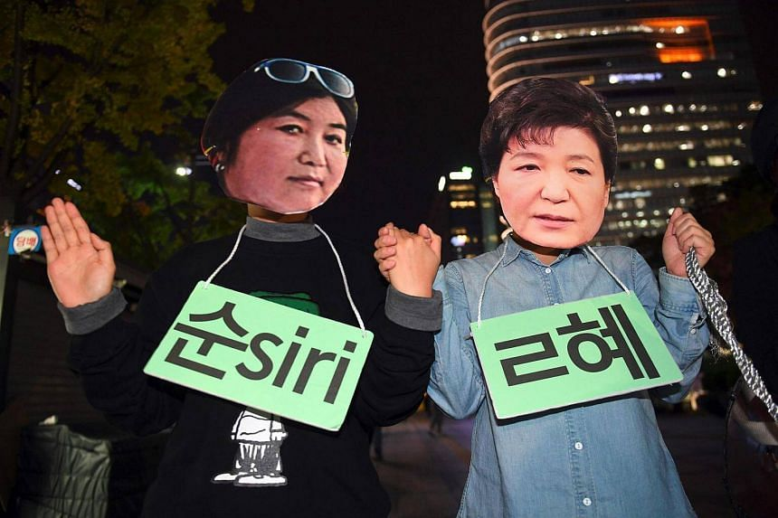 Protestors wearing masks of South Korean President Park Geun Hye (right) and her confidante Choi Soon Sil (left) posing for a performance during a rally denouncing a scandal over President Park's aide in Seoul on Oct 27, 2016.