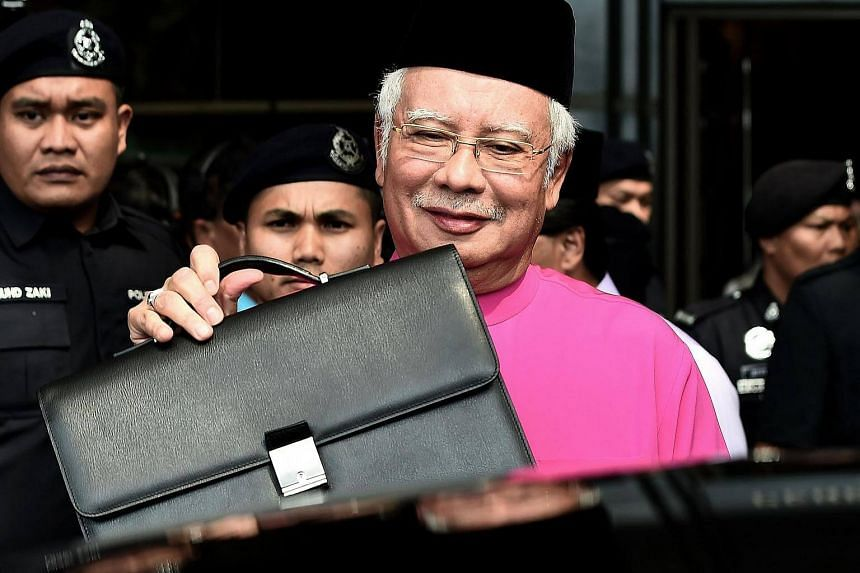 Malaysia's Prime Minister Najib Razak posing with his briefcase as he leaves to unveil the 2017 financial budget to Parliament House, outside the Finance Ministry in Putrajaya, on Oct 21, 2016.