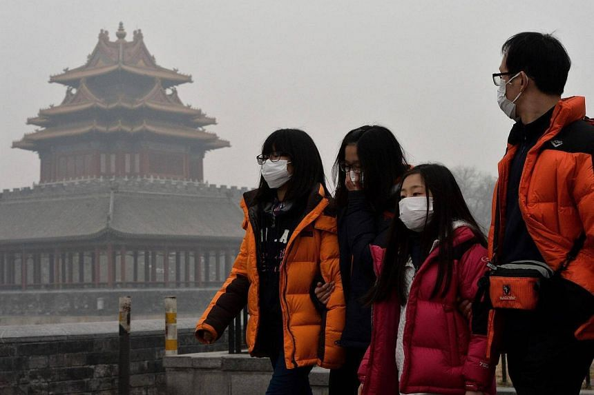 Chinese tourists with face masks walking past the Forbidden City as heavy air pollution continues to shroud Beijing.