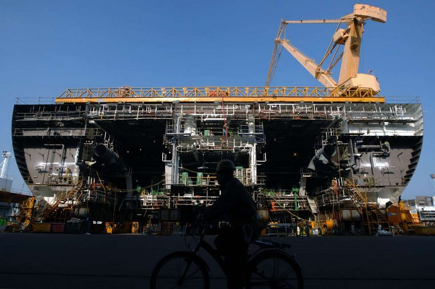 A man cycles past a ship under construction at the Daewoo Shipbuilding & Marine Engineering Co. yard in Geoje, South Korea.