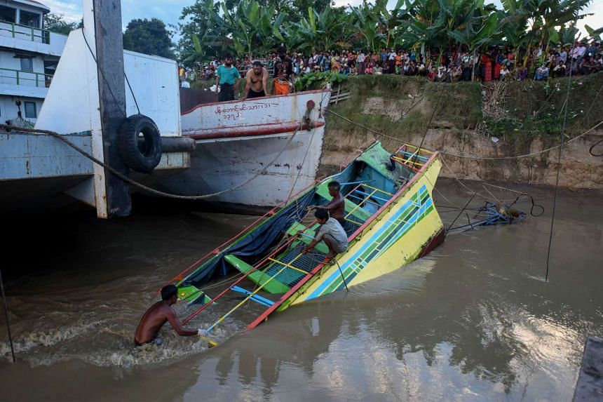 Rescue workers on the sunken ferry partially lifted from the water near the river bank on the Chindwin River in Sagaing region, Myanmar, on Oct 18, 2016.
