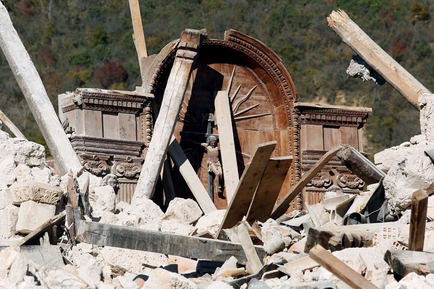 A crucifix is seen amid the rubble of San Salvatore church in the village of Campi near Norcia, on Oct 31, 2016.