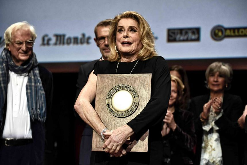 French actress Catherine Deneuve reacts after receiving the Lumiere Award during the Eighth edition of the Lumiere Film Festival, on Oct 14, 2016 in Lyon, central eastern France.