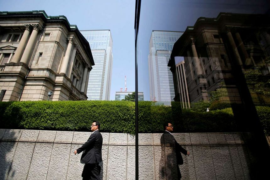A pedestrian walks past the Bank of Japan building in Tokyo.