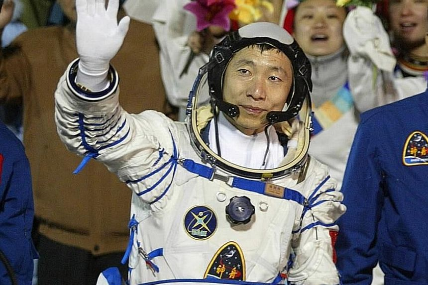 China's first female astronaut Liu (centre) on her return on June 29, 2012. Astronaut Yang was China's first man in space.