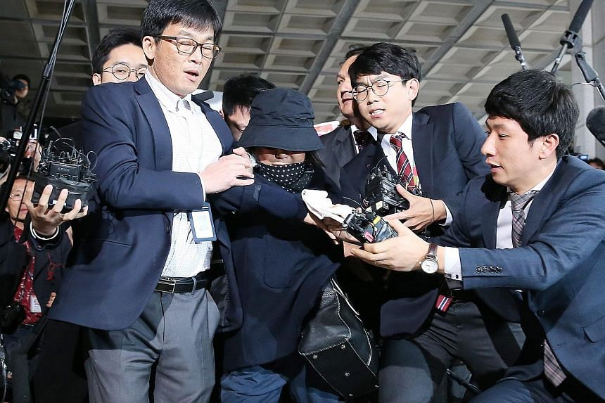 Ms Choi (wearing a hat) turned up at the Seoul Central District Prosecutor's Office yesterday, making her way through a mob of journalists. She is accused of using her close friendship with President Park to exert extensive influence over major gover