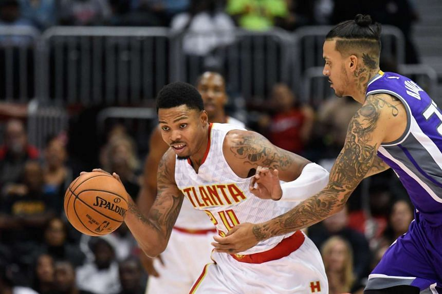 Atlanta Hawks forward Kent Bazemore (24) is defended by Sacramento Kings forward Matt Barnes (22) during the second half at Philips Arena. The Hawks defeated the Kings 106-95.