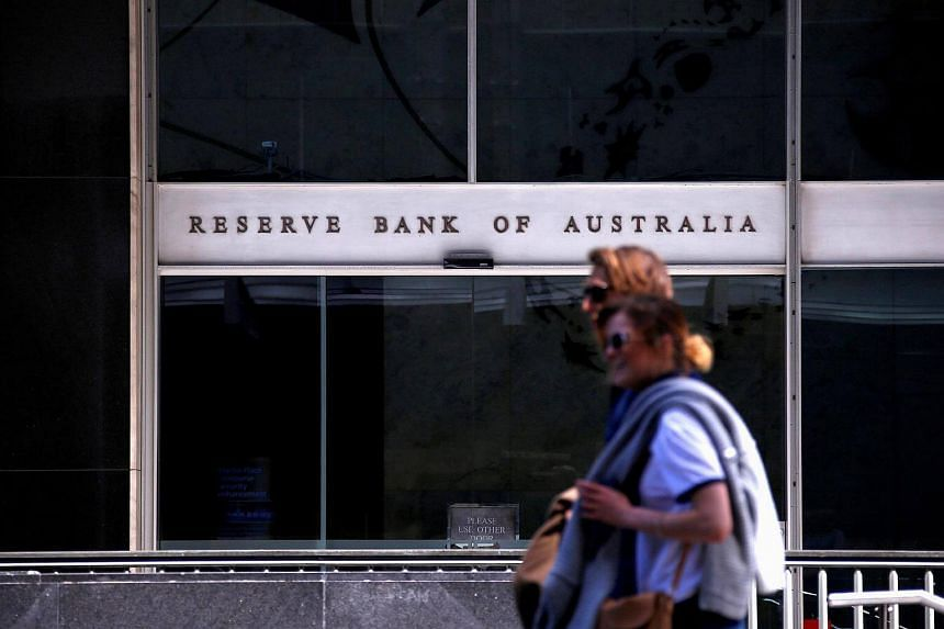 Pedestrians walk past the main entrance to the Reserve Bank of Australia's head office in Sydney.
