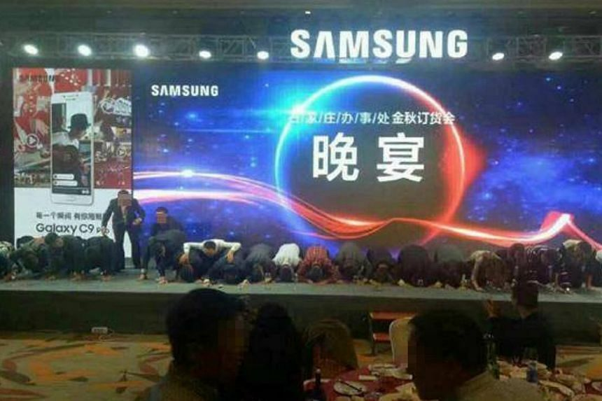 Samsung executives kowtowing to express their gratitude to phone distributors at a sales meeting in China.