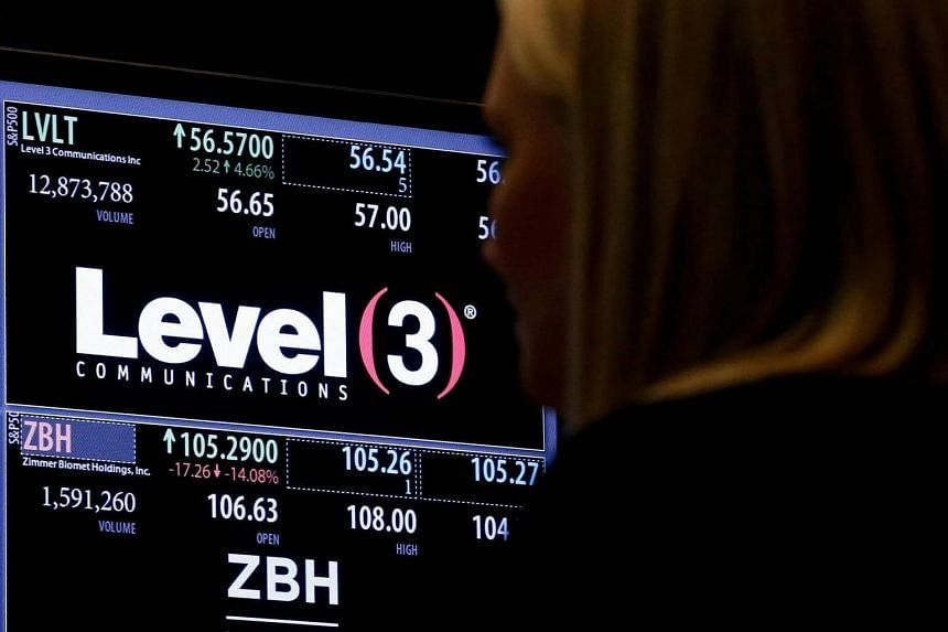 A trader passes by the post where Level 3 Communications is traded on the floor of the New York Stock Exchange.