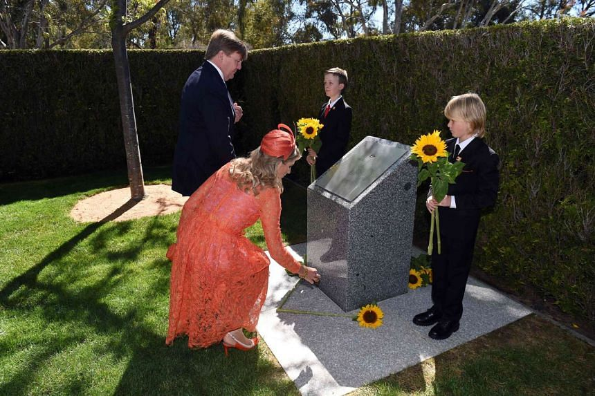 Dutch King Willem-Alexander and Queen Maxima place sunflowers at the MH17 Memorial at Parliament House in Canberra on Nov 2, 2016.