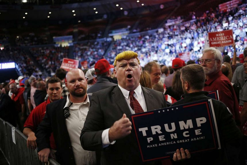 An attendee wearing a plastic molded wig is escorted from the venue by security officers during a campaign event for Donald Trump, 2016 Republican presidential nominee, in Cincinnati, Ohio, US on Oct 13, 2016.