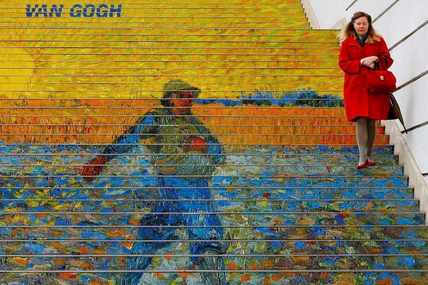 A woman walks down stairs advertising a Vincent van Gogh exhibition outside Albertina museum in Vienna, Austria on Oct 20, 2016.