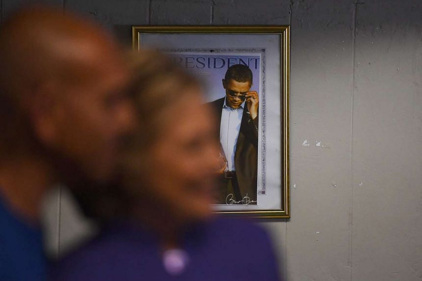 A framed picture of US President Barack Obama is seen on the wall as US Democratic presidential nominee Hillary Clinton greets patrons at a restaurnat in Fort Lauderdale, Florida, on Oct 30, 2016.