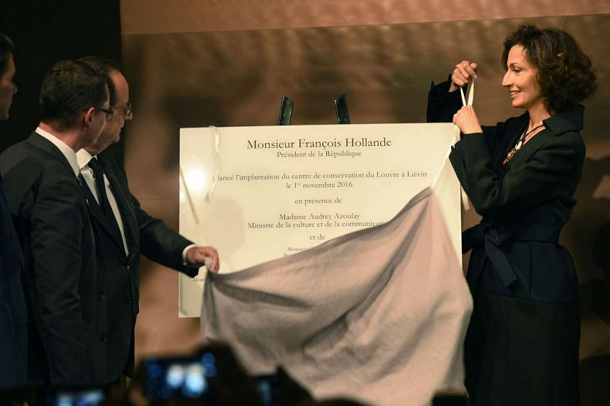 French president François Hollande and French Culture minister Audrey Azoulay (right) unveil a plaque launching the Conservation centre of the Louvre on Nov 1, 2016 at the Louvre Lens museum in Lens, northern France.