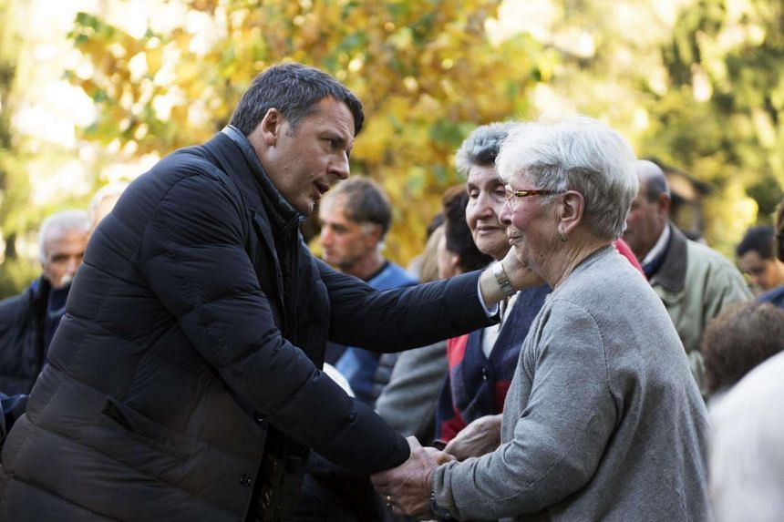 Italian Prime Minister Matteo Renzi (left) meets with residents during his visit in Preci, Perugia, Italy, on Nov 1, 2016.