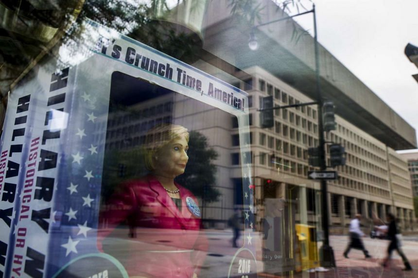 The FBI Headquarters are reflected in a window of a store selling political souvenir of Democratic Presidential nominee Hillary Clinton in Washington, DC, USA, on Nov 1, 2016.