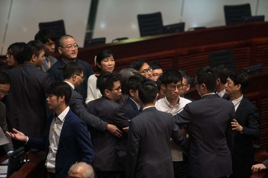 Security guards try to remove Mr Baggio Leung from the chamber.