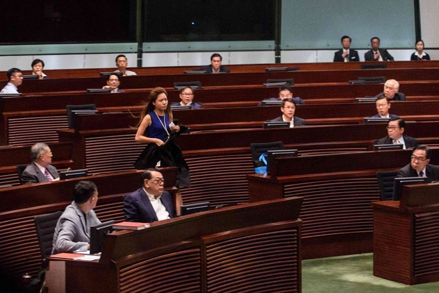 Ms Yau Wai Ching runs into the chamber before attempting to take her oath.