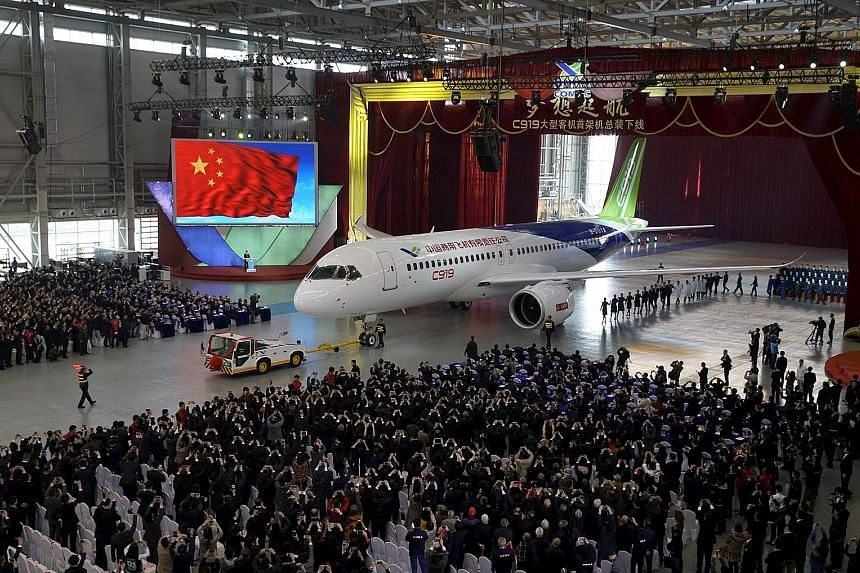 The C919 passenger jet on show during a news conference at Comac's Shanghai factory last year. The plane is part of a plan by Mr Xi to transform China from a maker of sneakers, apparel and toys into one that can compete with the likes of Airbus and B