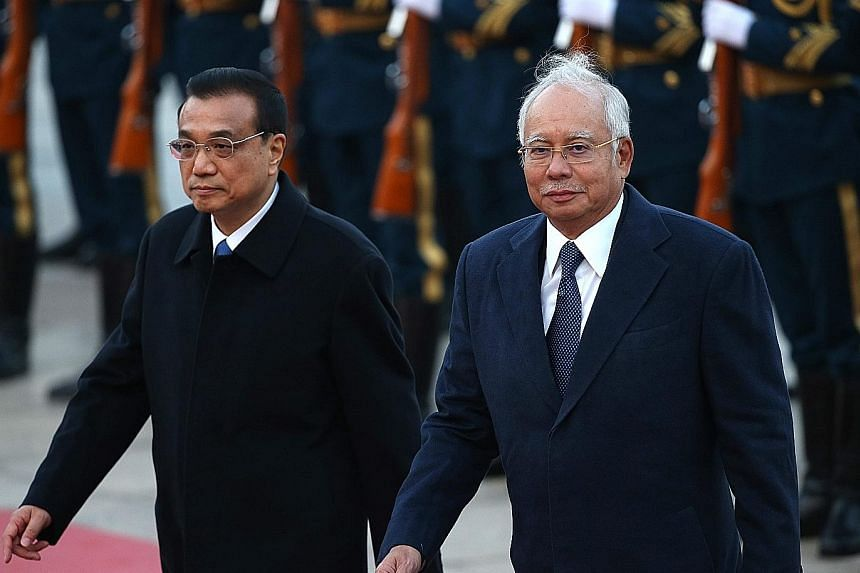 Mr Najib Razak and Mr Li Keqiang reviewing honour guards in Beijing yesterday. Nine government-to-government pacts and five business cooperation deals were signed as part of Mr Najib's visit.