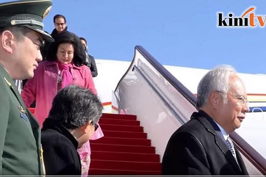 A screenshot showing Mr Riza (background) emerging from the Malaysian delegation's plane in Beijing on Monday behind his mother.