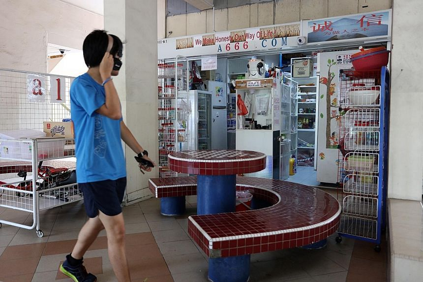 """At the """"no shopkeeper"""" provision store in Hougang (left), customers pay for their items at a self-service cash register (above). They put the cash into a slot after showing the price tag to one of eight CCTV cameras. The owner made the machine for le"""