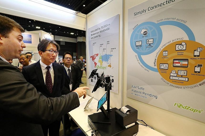 """Mr Lim (centre) being shown a workflow management platform for the F&B sector at the Singapore Productivity Conference and Exhibition yesterday. The Manpower Minister said that Singapore offers a competitive proposition now, with """"products and servic"""