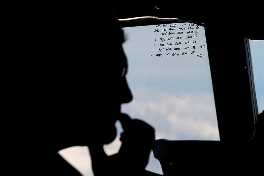 A crew member aboard a Royal New Zealand Air Force P-3K2 Orion aircraft is pictured alongside handwritten notes of other search craft in the area, during a search for the missing Malaysian Airlines MH370 over the Indian Ocean.