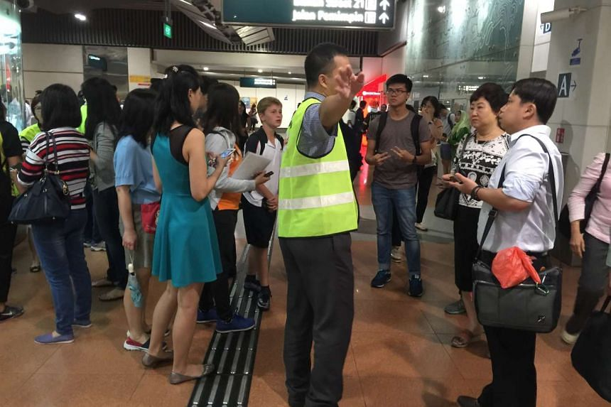 An SMRT staff member providing assistance to members of the public at Marymount MRT station.