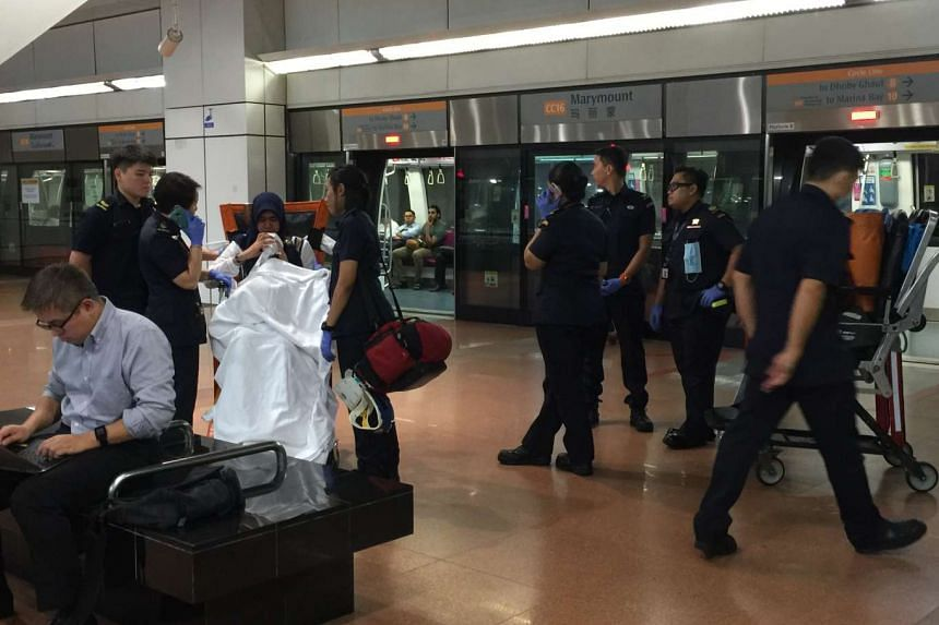 SCDF officers tend to a lady who was not feeling well at the station.