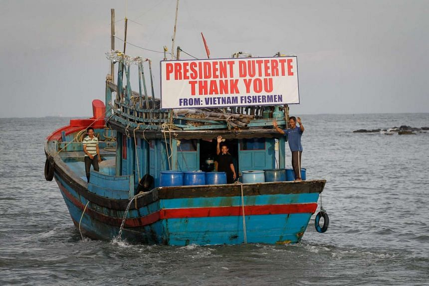 Vietnamese fishermen wave goodbye on their fishing vessels during a send-off ceremony in Sual province, Pangasinan, Philippines on Nov 2, 2016.