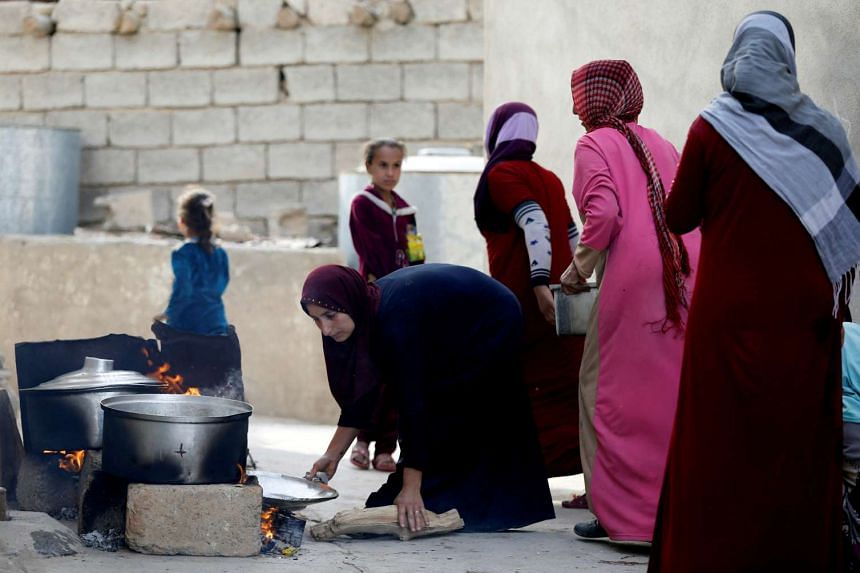 Civilians cook for the Iraqi army after the liberation of Khalidiya village from ISIS militants, south of Mosul.