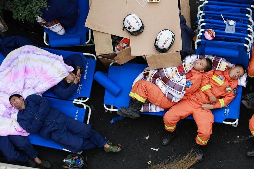 Rescuers rest near the site of an explosion at a coal mine in Chongqing, China.