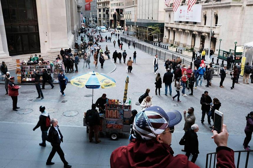 People walk outside of the New York Stock Exchange (NYSE) on Nov 1, 2016, in New York City.