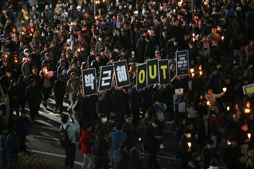 Protesters shout slogans and hold placards reading 'Park Geun Hye Out' during a protest against South Korean President Park Geun Hye on the main street in Seoul, South Korea, on Oct 29, 2016.