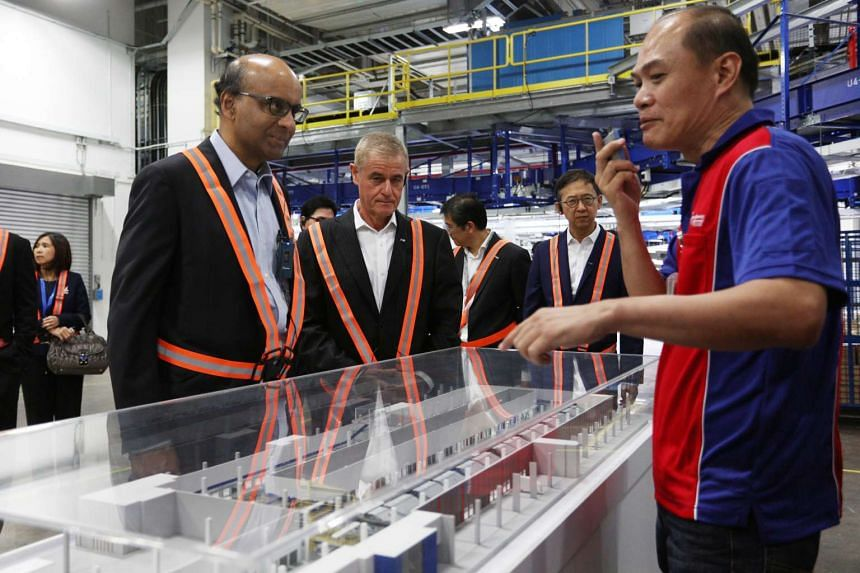 Mr Tharman and SingPost chairman Simon Israel with a logistics employee as he explained the parcel-sorting automation process at SingPost's new regional e-commerce logistics hub in Tampines yesterday.