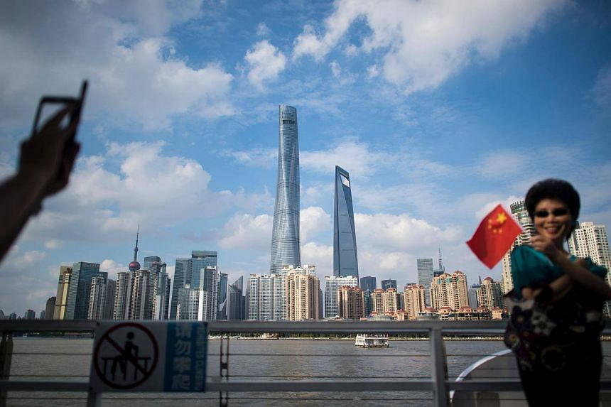 A woman poses for a picture with a Chinese flag in front of the skyline of the financial district in Shanghai.