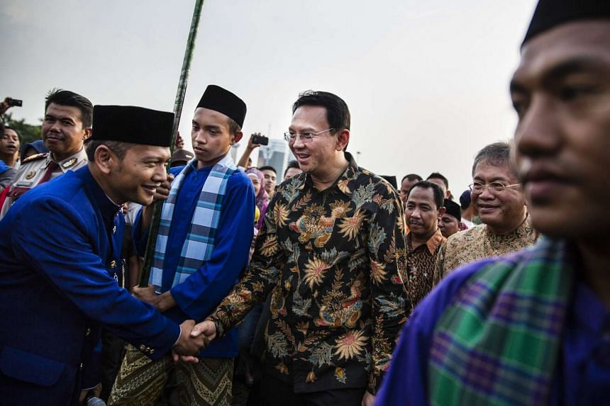 Basuki Tjahaja Purnama, the governor of Jakarta, greets people after arriving at National Monument in Jakarta on June 10, 2014.