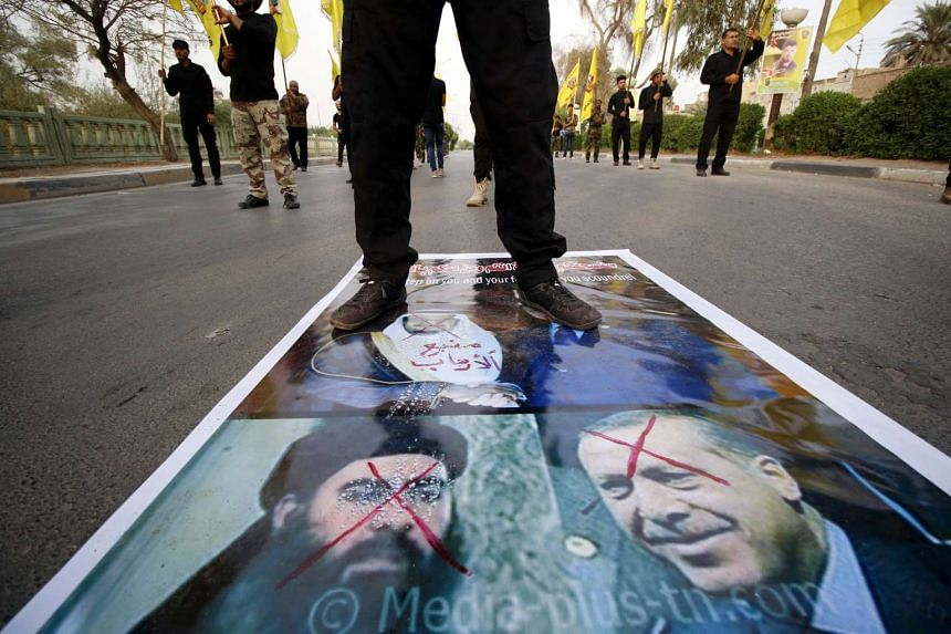 A protester stands on a picture of Turkey's President Tayyip Erdogan and Islamic State leader Abu Bakr al-Baghdadi, in Basra, Iraq on Oct 19, 2016.