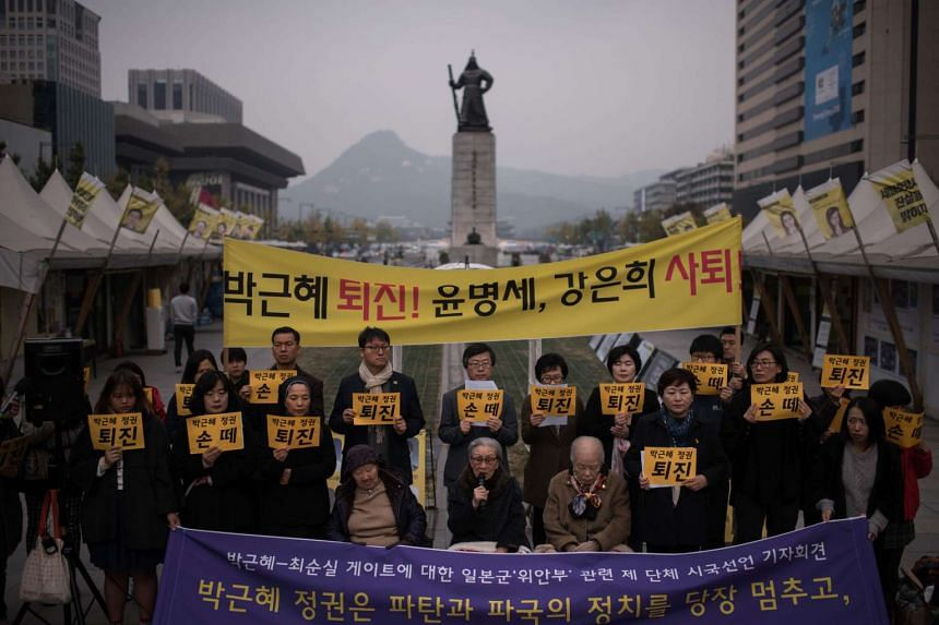 """Protesters hold placards reading """"Park Guen-Hye resign!"""" as they stand in Gwanghwamun square in central Seoul."""