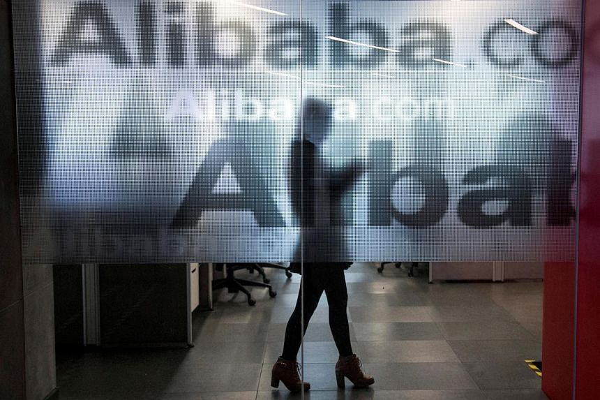 An employee behind a glass wall with the logo of Alibaba at the company's headquarters.
