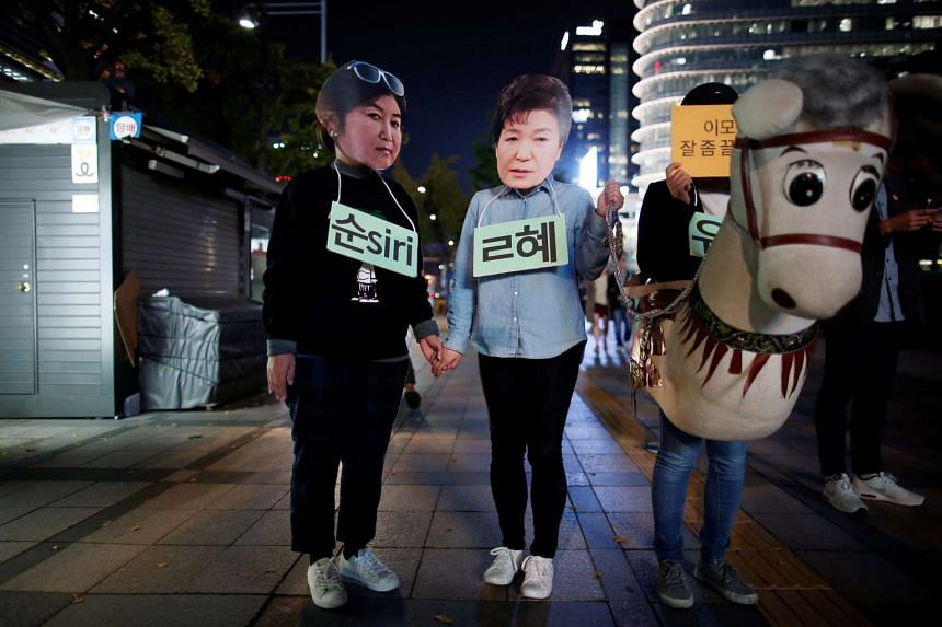 Protesters wearing cut-out of South Korean President Park Geun Hye (centre) and Choi Soon Sil attend a protest denouncing Ms Park over an influence-peddling scandal in central Seoul on Oct 27, 2016.