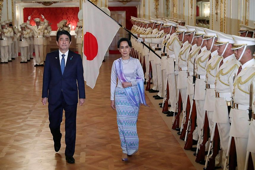 Myanmar State Counselor Aung San Suu Kyi (centre), accompanied by Japan's Prime Minister Shinzo Abe, reviews a guard of honor before their meeting at the state guest house in Tokyo, Japan on Nov 2, 2016.