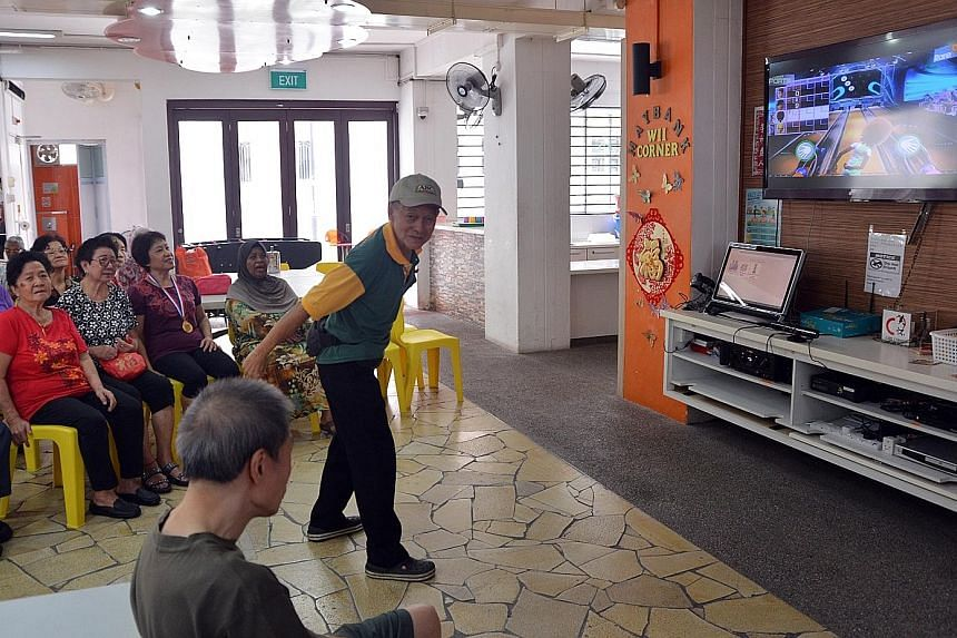 Mr Eng (centre) striking a pose while playing Kinect Bowling at the senior activity centre at the void deck of Block 170 in Lorong 1, Toa Payoh. The activity is held every Thursday from 10am to noon, and about 16 people are selected to play. Voluntee