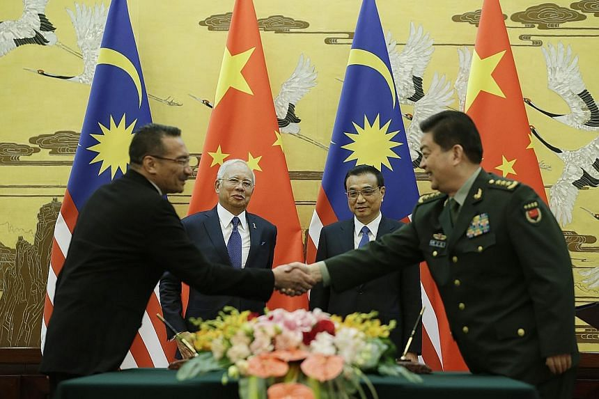 Malaysian Prime Minister Najib Razak and Chinese Premier Li Keqiang observe as Malaysian Defence Minister Hishammuddin Hussein and China's Defence Minister Chang Wanquan shake on a deal in Beijing on Tuesday.