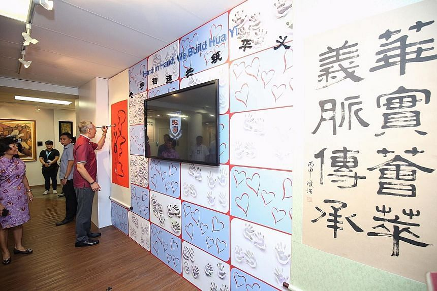 PM Lee adding a final touch to a calligraphy piece while on tour of Hua Yi Secondary School yesterday.